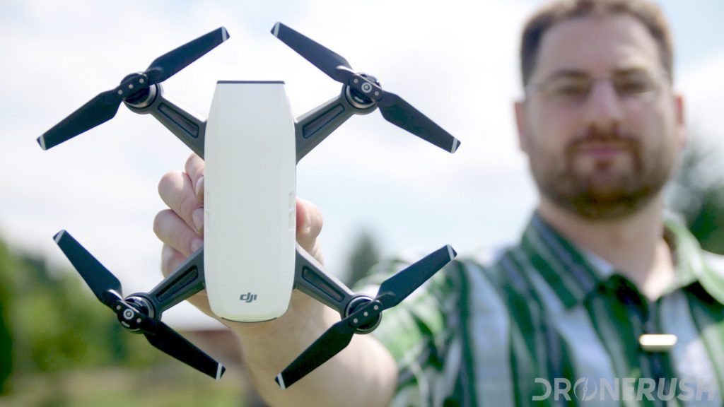A photo of Jonathan holding up a white DJI Spark, standing in a football field. One of the best mini drones on the market today.