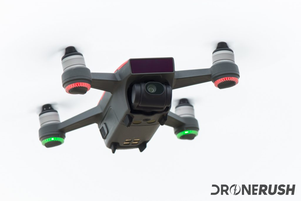 For our DJI Spark review, this is a red DJI Spark hovering in the air on an overcast day at the beach.