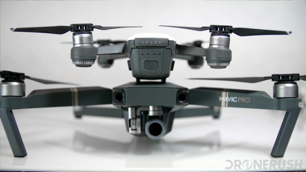 A white DJI Spark sits on top of a standard DJI Mavic Pro drone, these are drones that you can control with the DJI GO 4 app or one of the best DJI GO 4 app alternatives.