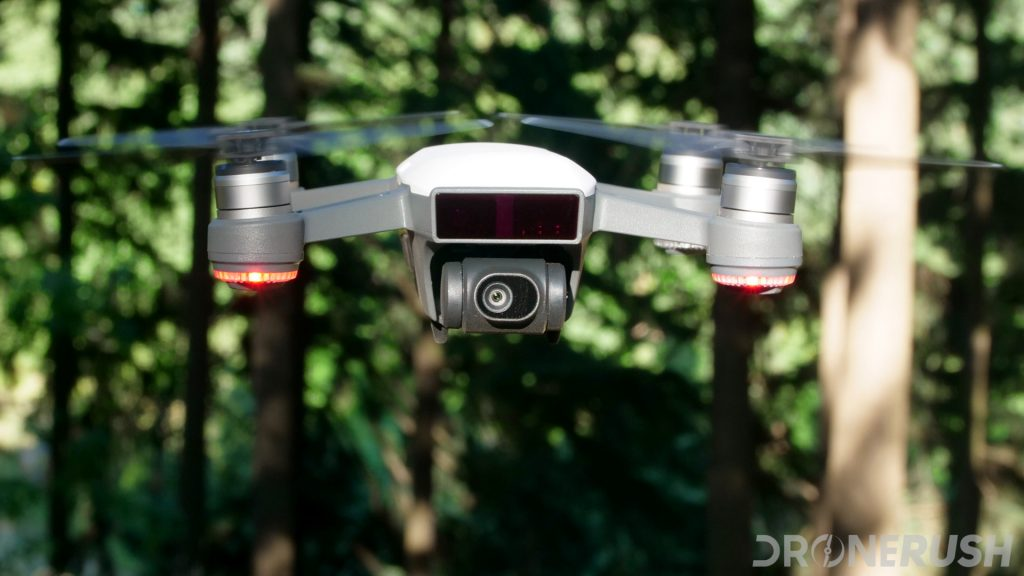 Image of a white DJI Spark hovering in front of trees, the drone is facing the camera so to show off the drone's camera, this is our DJI Spark camera review.