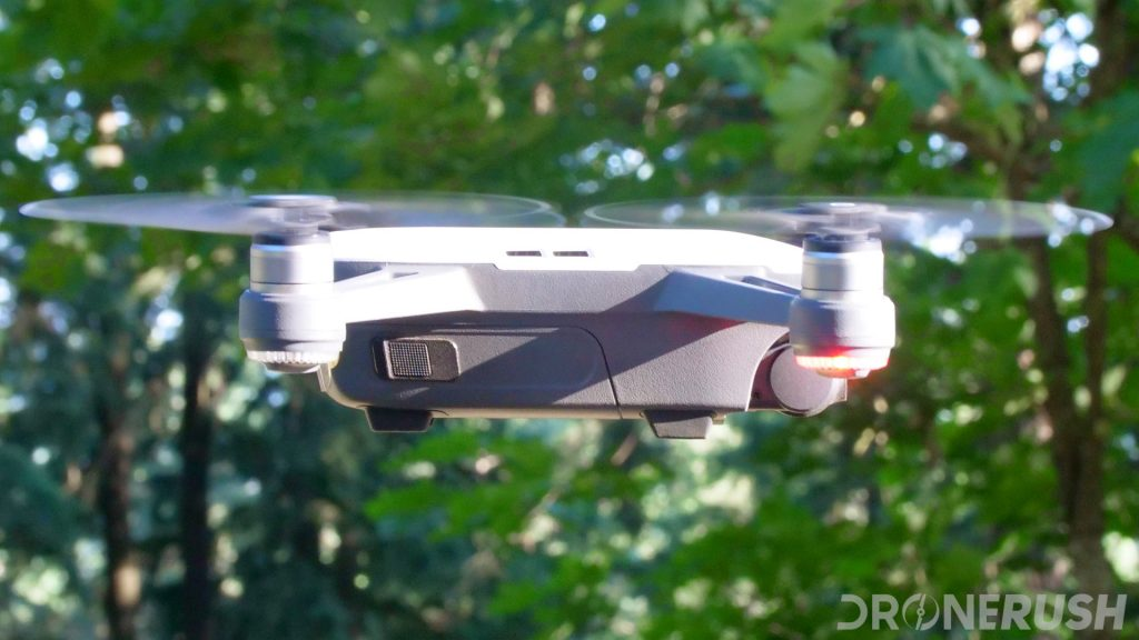 A white DJI Spark compact drone flying in front of trees. Side view of the drone. Let's explore some reasons to choose the DJI Spark.