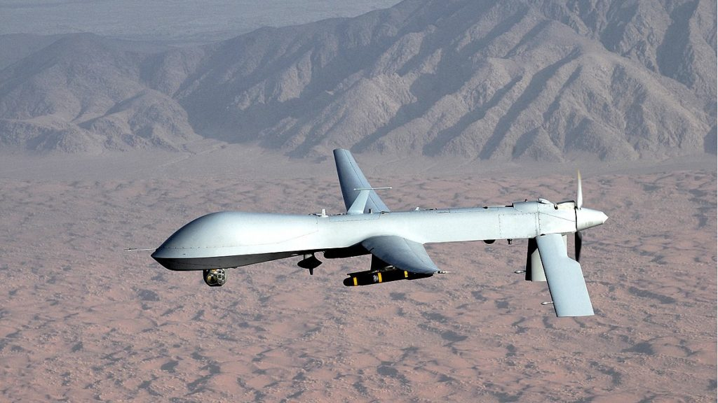 An armed Predator drone flying a military drone operation over the desert.