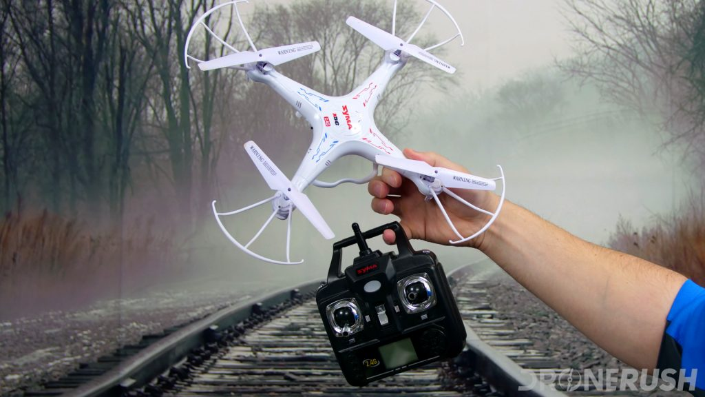 Syma X5C explorer edition toy drone and remote control held up in hand in front of a photo backdrop.