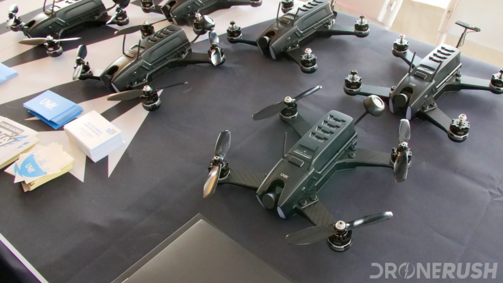 A table full of drones. The Uvify Draco racing drone and Uvify Draco HD digital racing drone laied out on a table at the Drone Rodeo at CES 2018.