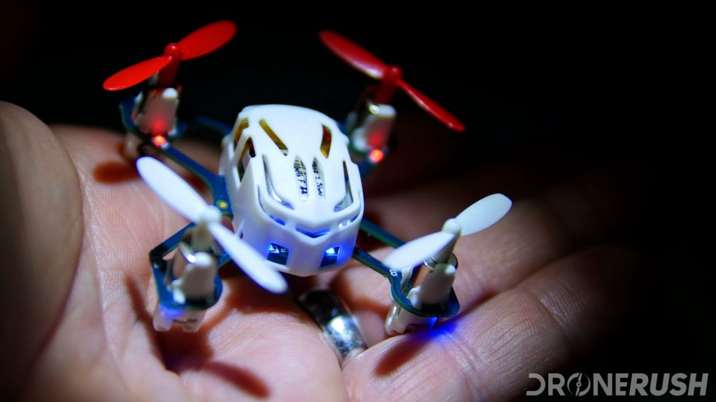 Holding the Hubsan H111 nano drone in my hand in the dark with a sharp spotlight to make it visually pop out. This is one of the best nano drones around, and it's in Drone Rush red and white colors.